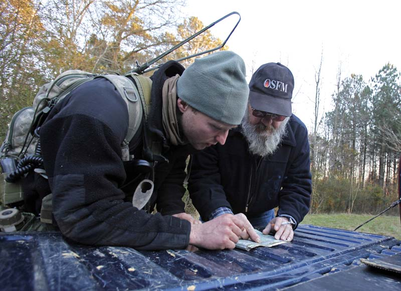 ** AADVANCE FOR WEEKEND, JULY 4-5 **In this Jan. 14, 2009 photo, Bob Snyder, also known as Pineland Bob, right, maps out a transportation plan with a soldier during the Special Forces' Robin Sage exercise in Ramseur, N.C. (AP Photo/Gerry Broome)