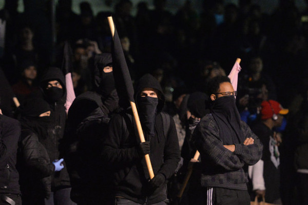 Members of the black bloc stand at Sproul Plaza during a protest against right-wing Milo Yiannopoulos who was scheduled to speak at UC Berkeley in Berkeley, Calif., on Wednesday, Feb. 1, 2017. (Doug Duran/Bay Area News Group)