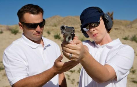 Man helping a woman with proper handgun marksmanship
